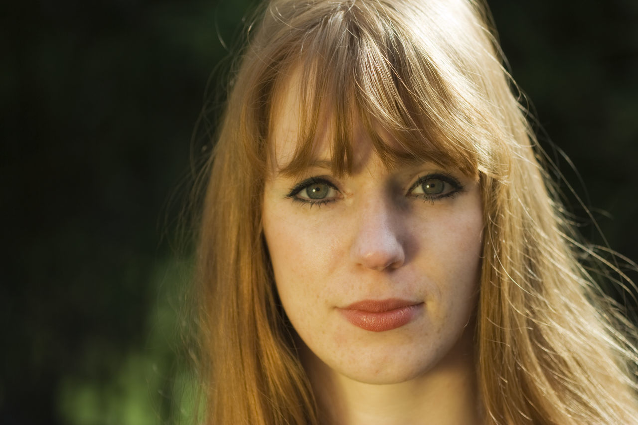 Close-Up Portrait Of Beautiful Woman With Bangs Outdoors