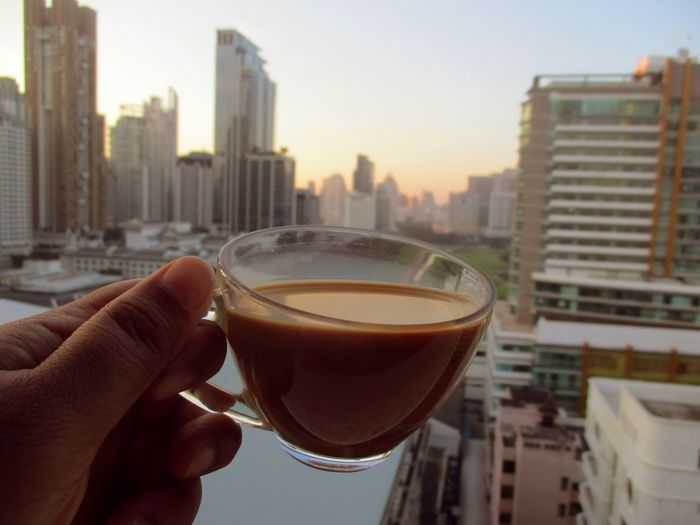 drink coffee on hight building Coffee Cup Coffee City Skyscraper Cityscape Drink Urban Skyline Building Exterior Architecture Human Hand Refreshment Human Body Part Built Structure Food And Drink City Life Roof Outdoors One Person Downtown District Sky Sunset