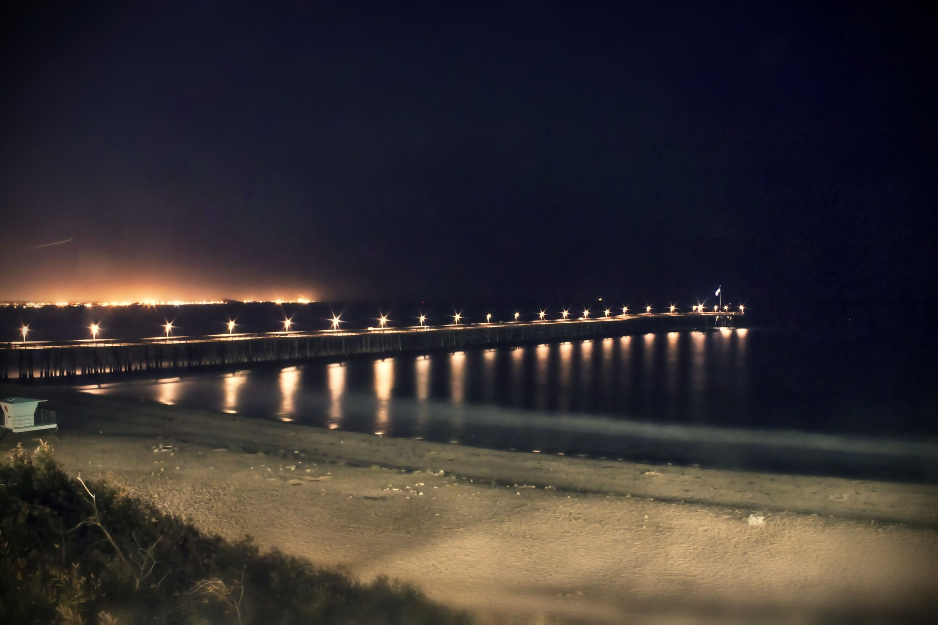 night, illuminated, water, built structure, architecture, reflection, river, bridge - man made structure, copy space, sea, sky, clear sky, connection, beach, city, bridge, street light, outdoors, shore, dusk