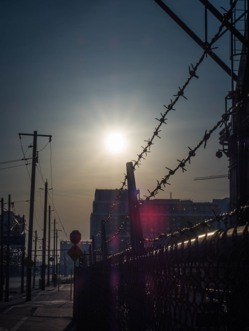 sun, lens flare, sunset, sunbeam, sunlight, building exterior, sky, real people, built structure, clear sky, outdoors, silhouette, city, architecture, men, electricity pylon, one person, standing, day, people