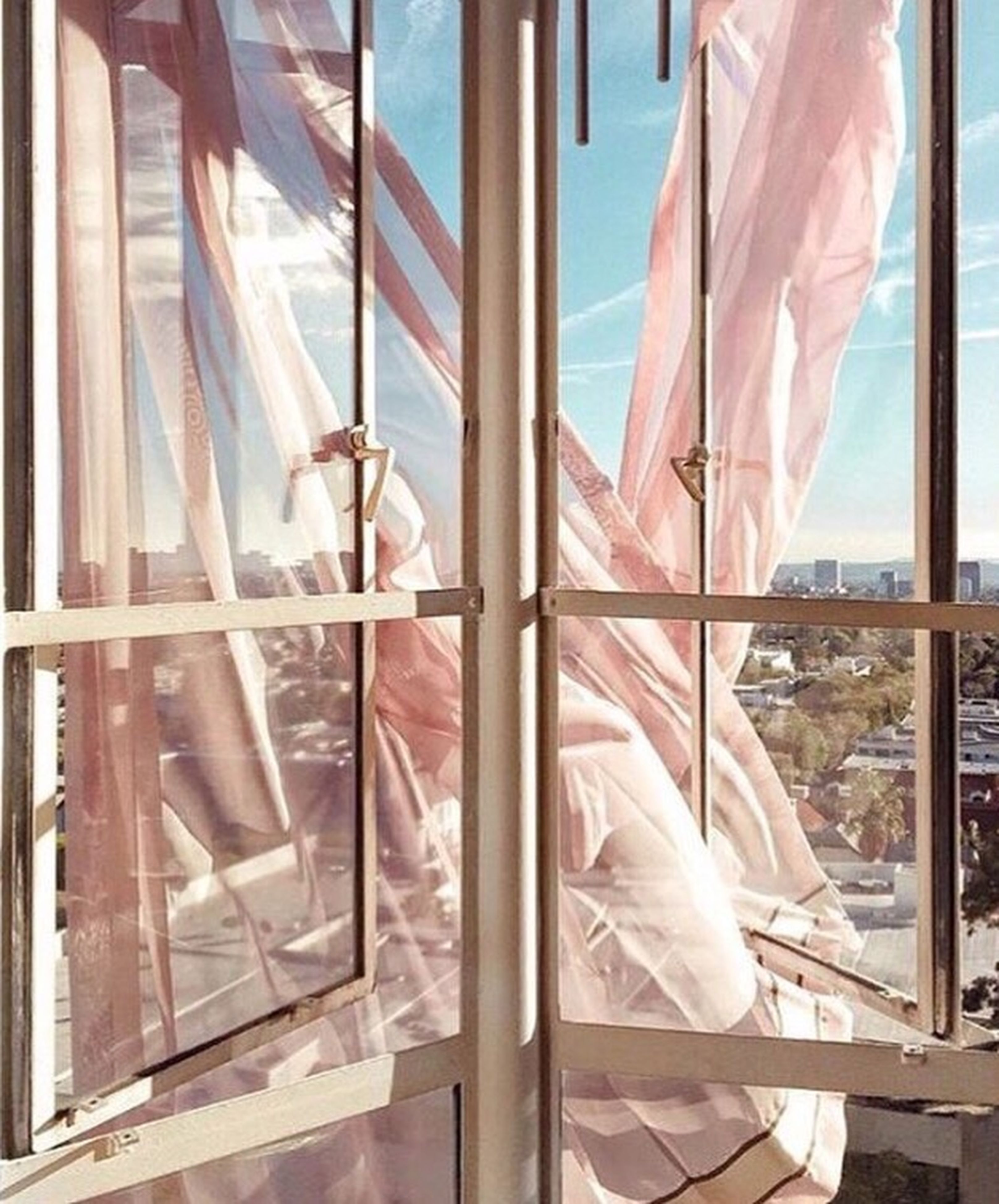 indoors, window, built structure, curtain, glass - material, low angle view, sunlight, day, architecture, part of, fabric, hanging, railing, transparent, metal, textile, rope, sky