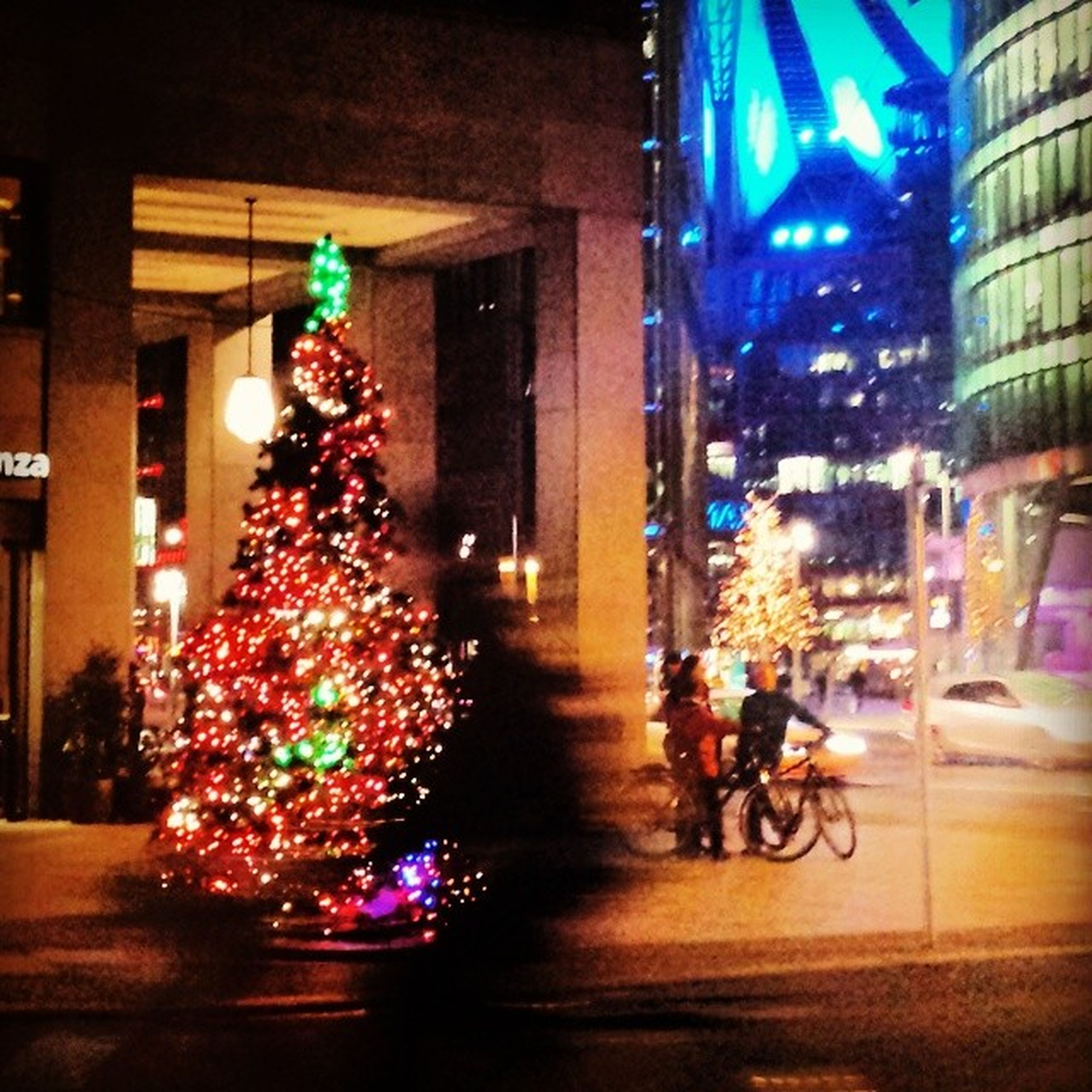 illuminated, night, decoration, christmas, architecture, built structure, building exterior, christmas tree, christmas decoration, celebration, city, lighting equipment, christmas lights, street, multi colored, incidental people, city life, celebration event, light - natural phenomenon, tradition