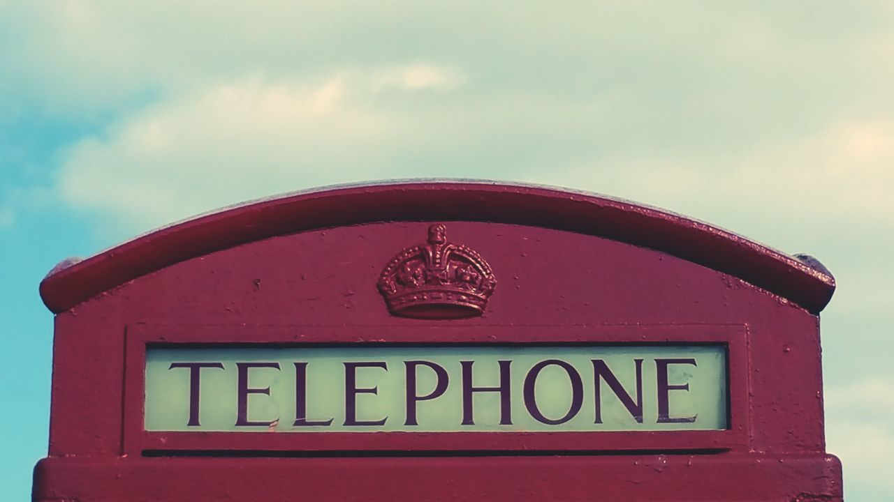 Close-Up Of Red Telephone Box Against Cloudy Sky