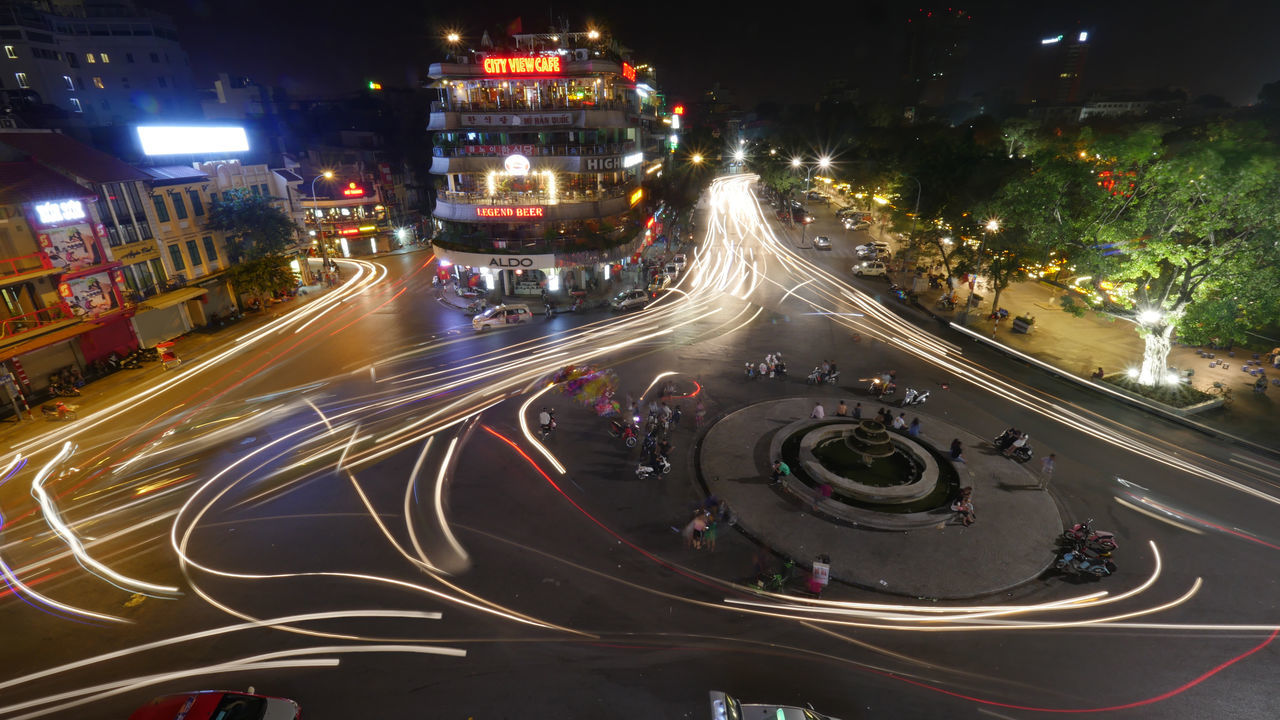 HANOI, VIETNAM - OCTOBER 27, 2015: Transport traffic with illuminated motion traces around the fountain on the square in city centre Architecture ASIA Car City City Life Fountain Hanoi Horizontal Illuminated Metropolis Night Nightlife Outdoors Road Sky Speed Street Street Light Traffic Transportation Vietnam