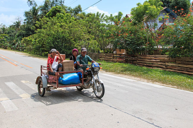 Puerto Princesa, Philippines - January 12,2015: Three people on a tricycle in the Philippines ASIA Beach Corong Corong Day Driving El Nido Full Length Land Vehicle Men Mode Of Transport Motorcycle Nacpan On The Move Palawan Philippines Puerto Princesa Riding Road Shadow South East Asia Summer Transportation Tree Tropics Underground River