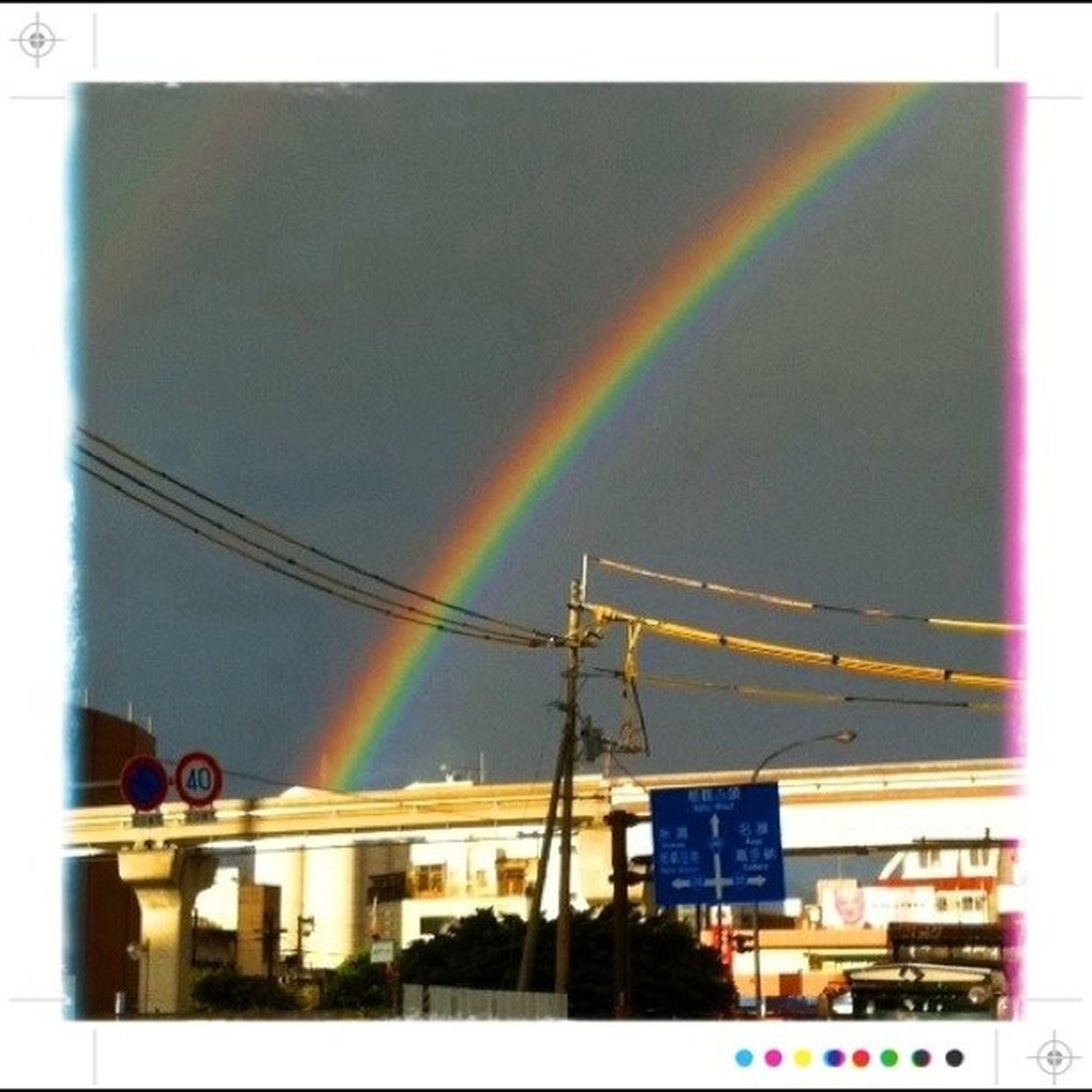 multi colored, sky, building exterior, built structure, architecture, transfer print, rainbow, auto post production filter, low angle view, city, no people, outdoors, cloud - sky, in a row, street light, day, power line, cable, illuminated, building