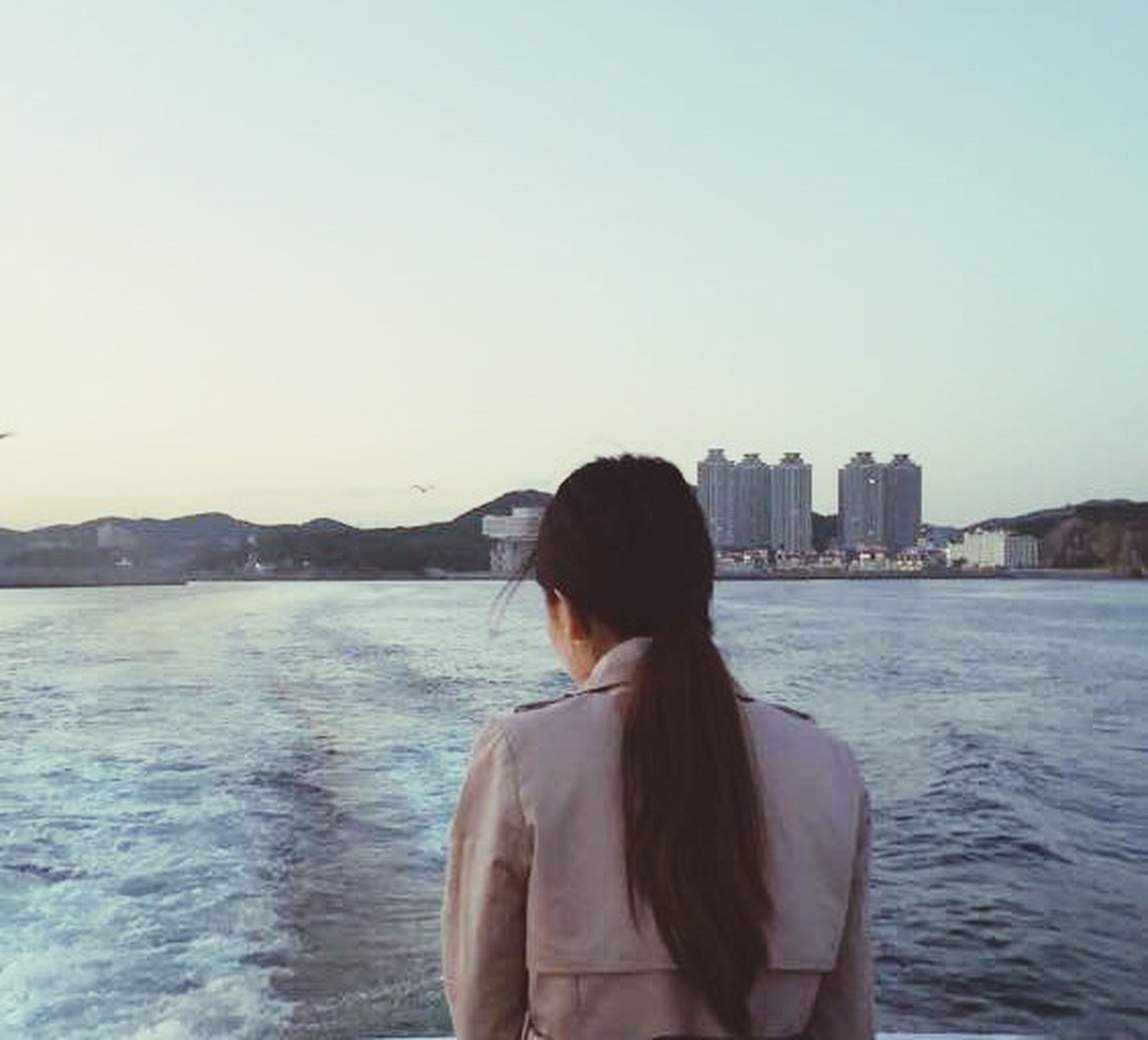water, rear view, clear sky, lifestyles, sea, waist up, copy space, leisure activity, standing, looking at view, three quarter length, young adult, casual clothing, built structure, building exterior, river, architecture, city