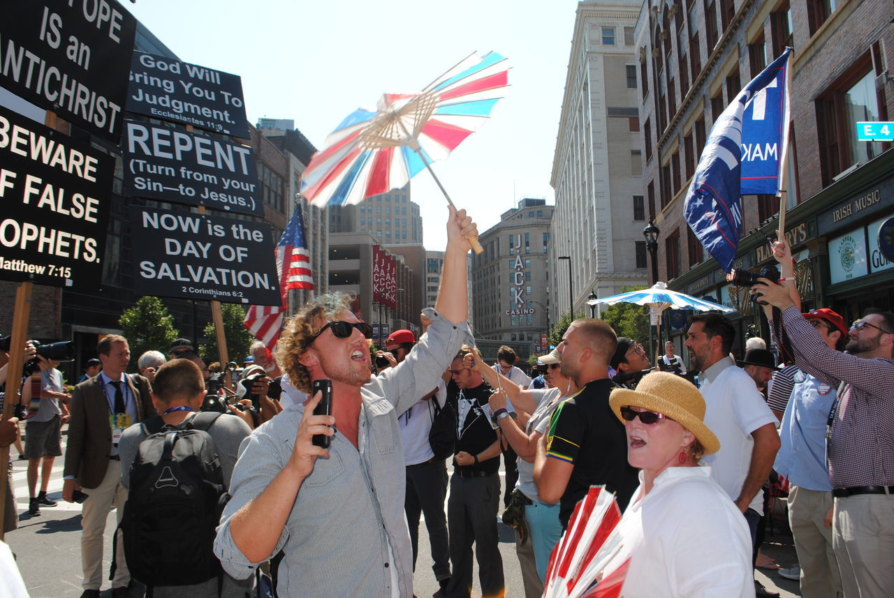 large group of people, flag, patriotism, real people, street, city, men, architecture, building exterior, built structure, women, celebration, outdoors, day, protestor, togetherness, crowd, adult, people