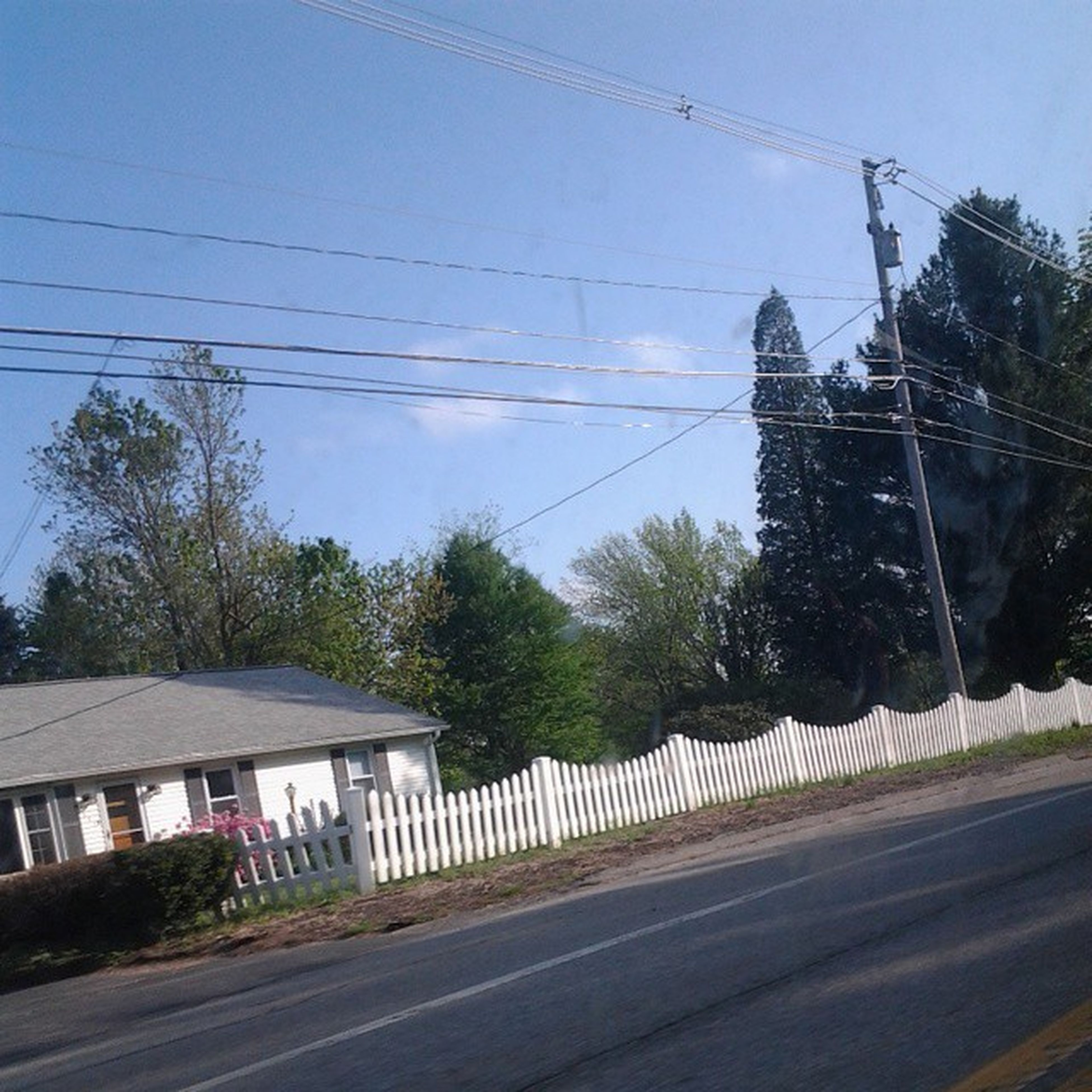 power line, transportation, built structure, architecture, electricity pylon, building exterior, road, clear sky, tree, cable, connection, street, sky, power supply, railroad track, electricity, power cable, road marking, day, outdoors