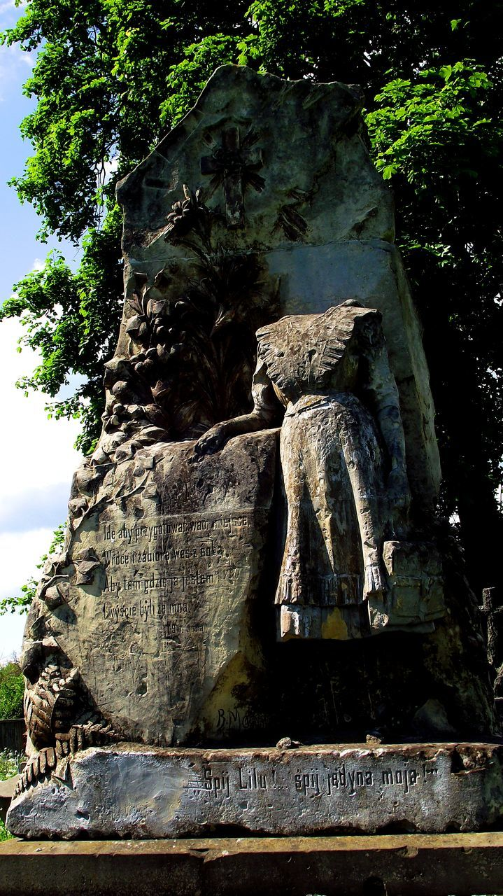 statue, sculpture, day, low angle view, tree, no people, nature, rock - object, outdoors, growth, beauty in nature, close-up, sky