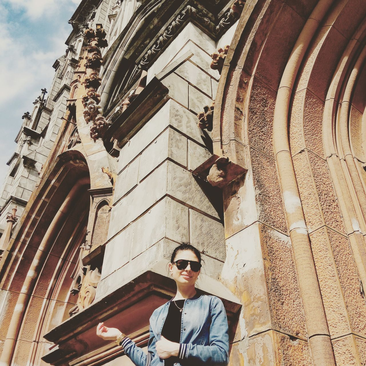 sunglasses, architecture, building exterior, built structure, real people, low angle view, young adult, one person, day, lifestyles, outdoors, portrait, sky
