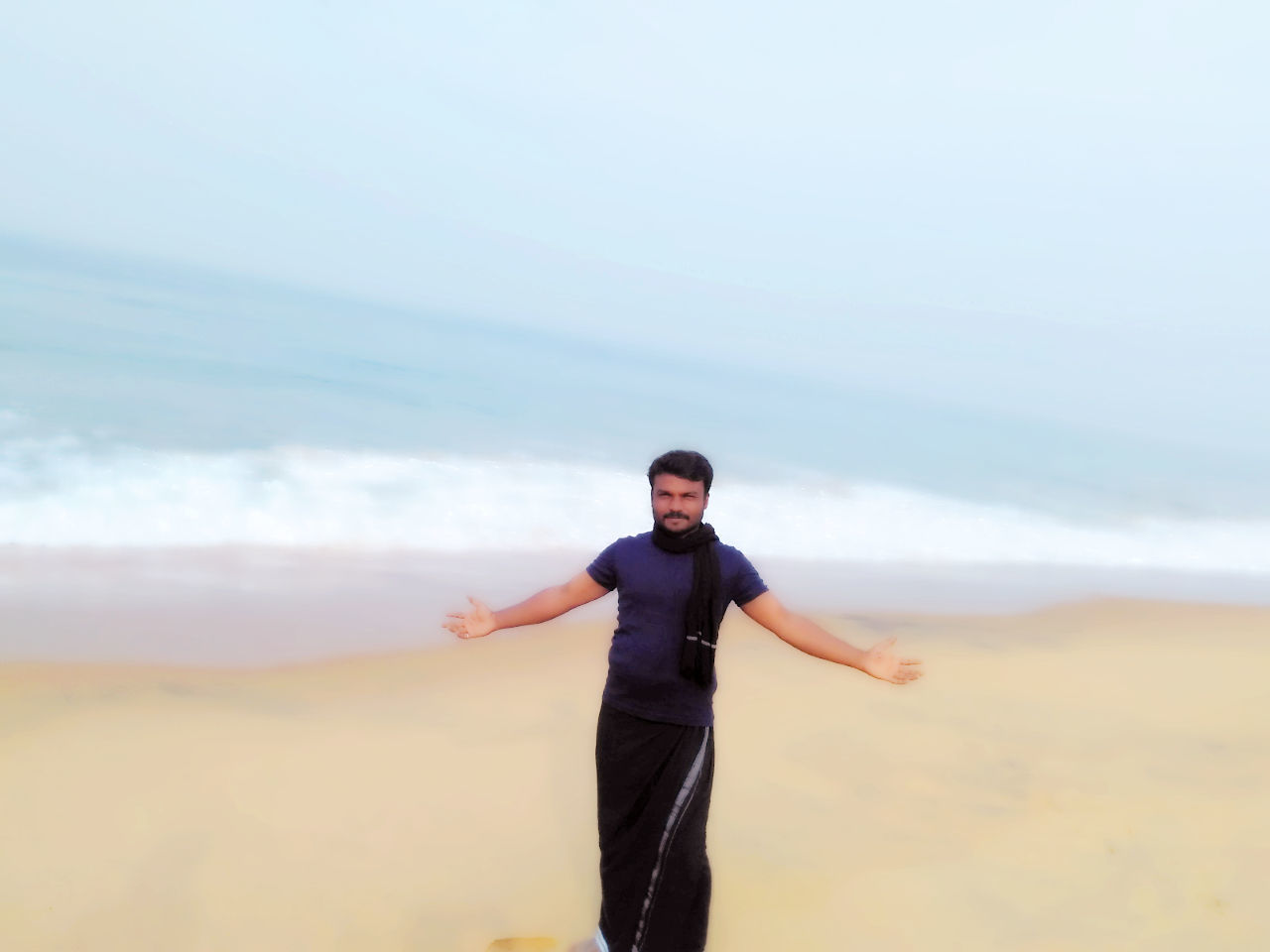 real people, sea, nature, one person, leisure activity, standing, sky, lifestyles, beach, front view, beauty in nature, outdoors, scenics, arms outstretched, sand, young men, horizon over water, looking at camera, day, water, focus on foreground, young adult, men, portrait, energetic