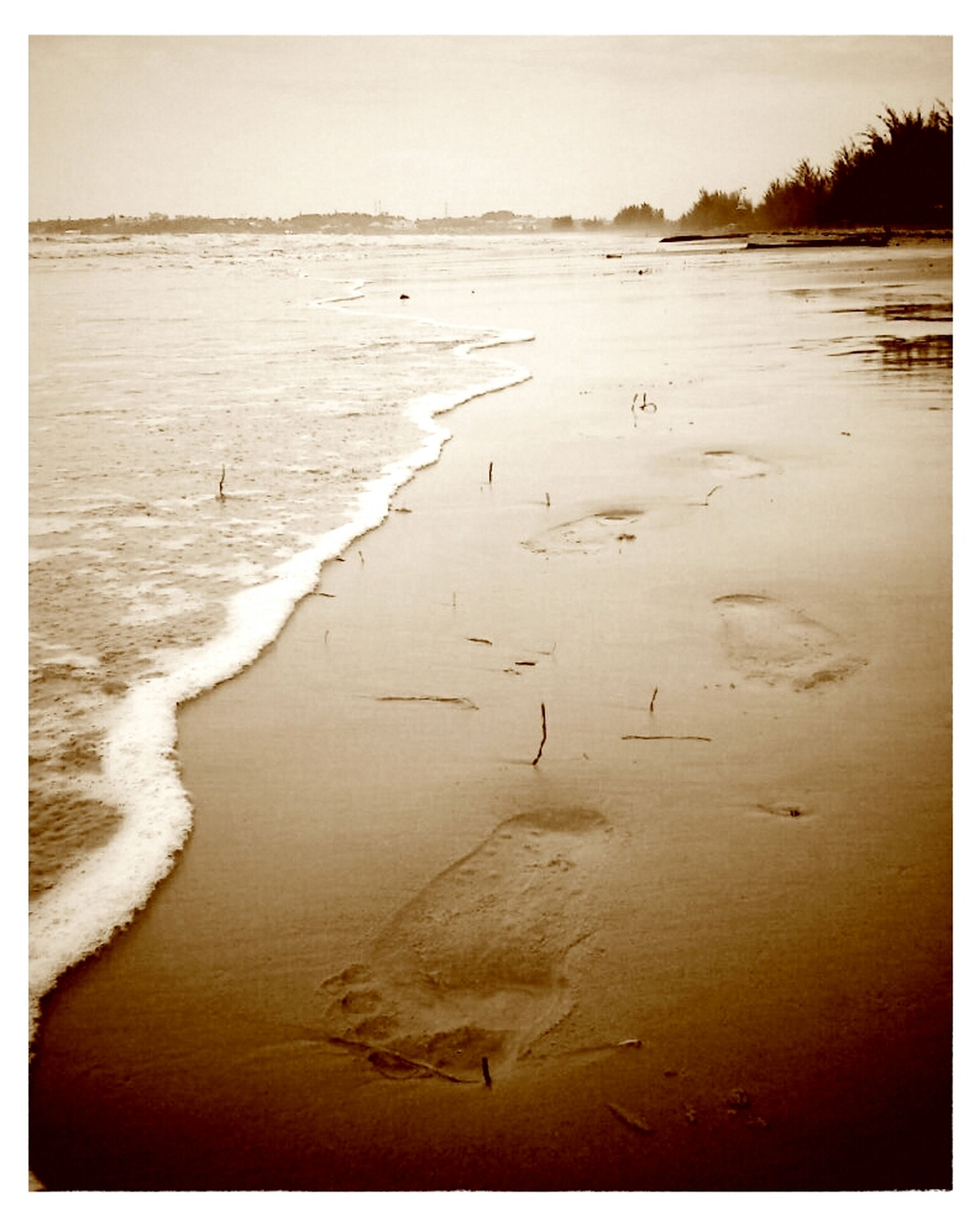 transfer print, sand, beach, water, auto post production filter, tranquility, shore, sea, tranquil scene, scenics, beauty in nature, nature, wave, footprint, coastline, surf, high angle view, idyllic, outdoors, non-urban scene