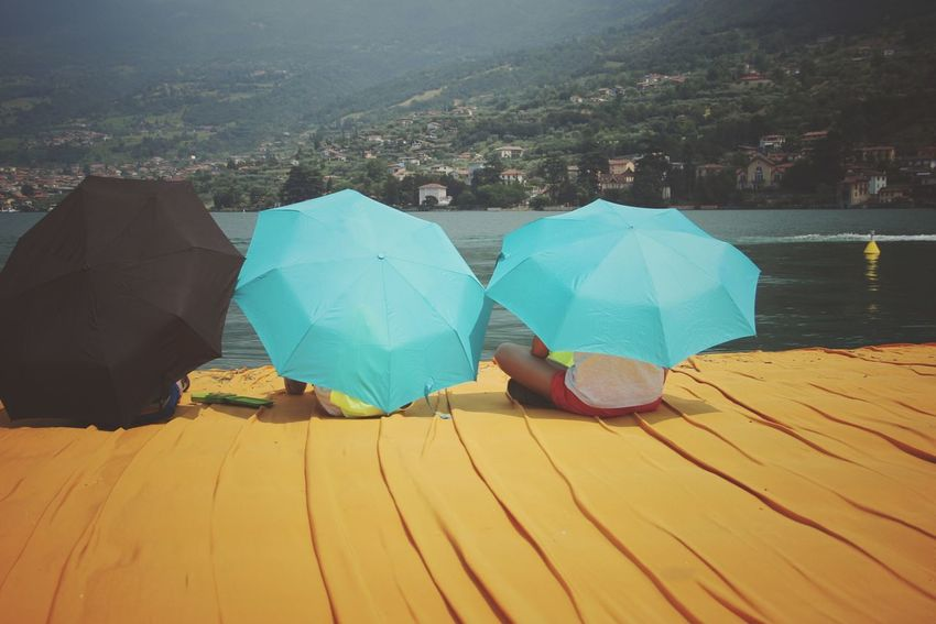 Walking on the Floating piers   Golden Moments  Relaxing Point Of View Tailored To You Umbrellas Sunshine Feel The Journey Christo And The Floating Piers Close-up The Essence Of Summer Getting Inspired Edge Of Imagination The Floating Piers Still Life Fine Art People The OO Mission 43 Golden Moments Showcase July Original Experiences Lake The Mix Up Lago D'Iseo EyeEm Italy  