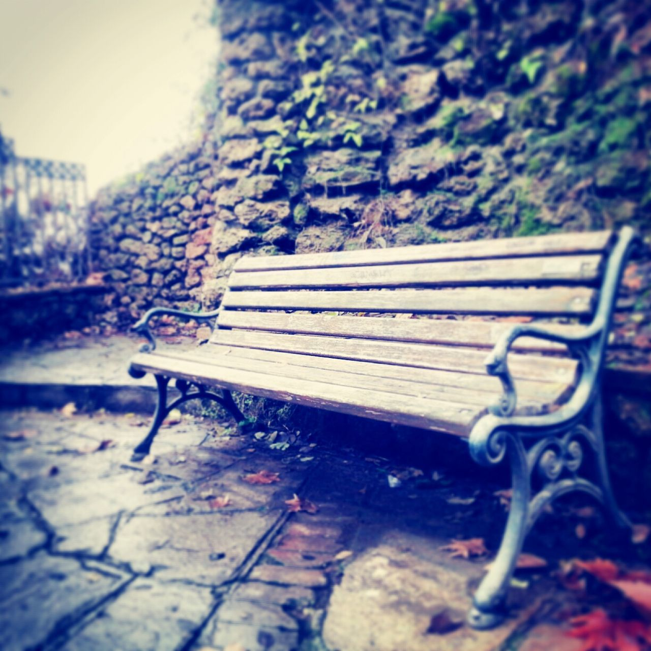 Empty Bench Against Stone Wall