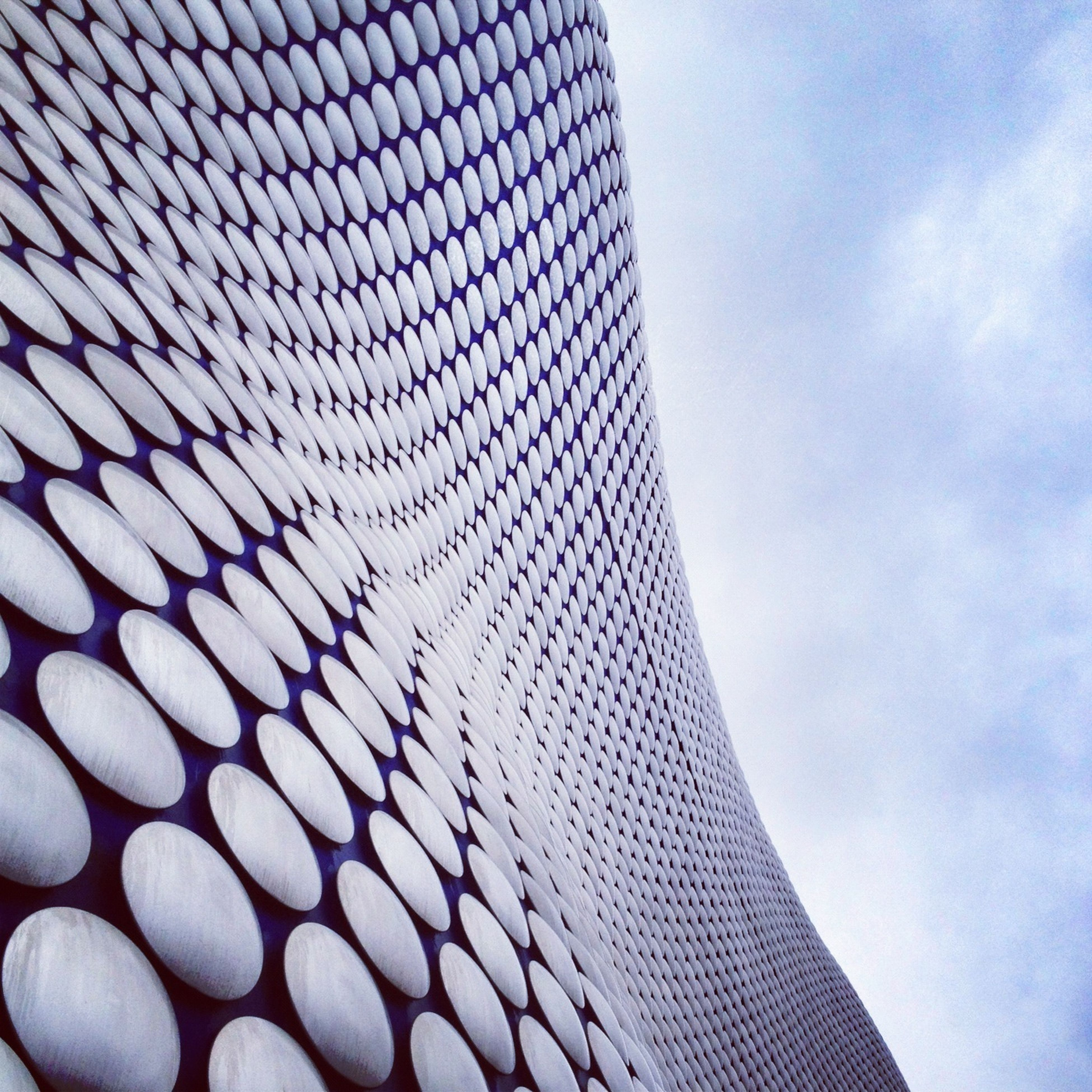 low angle view, sky, built structure, architecture, pattern, building exterior, cloud - sky, modern, day, outdoors, cloud, design, no people, blue, part of, office building, directly below, metal, architectural feature, close-up