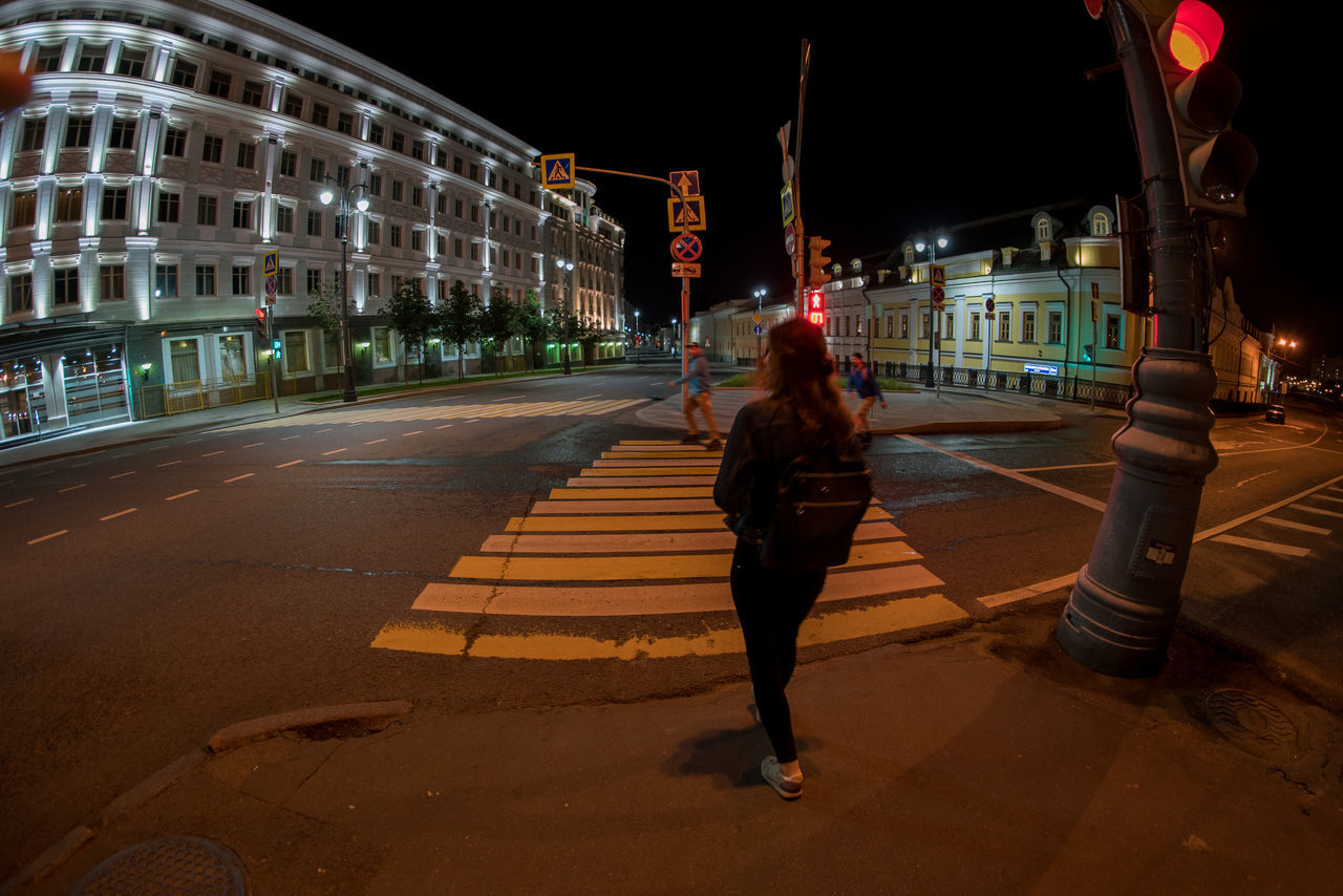 night, architecture, building exterior, street, built structure, transportation, illuminated, road, full length, city, outdoors, real people, walking, city life, one person, women, young adult, sky