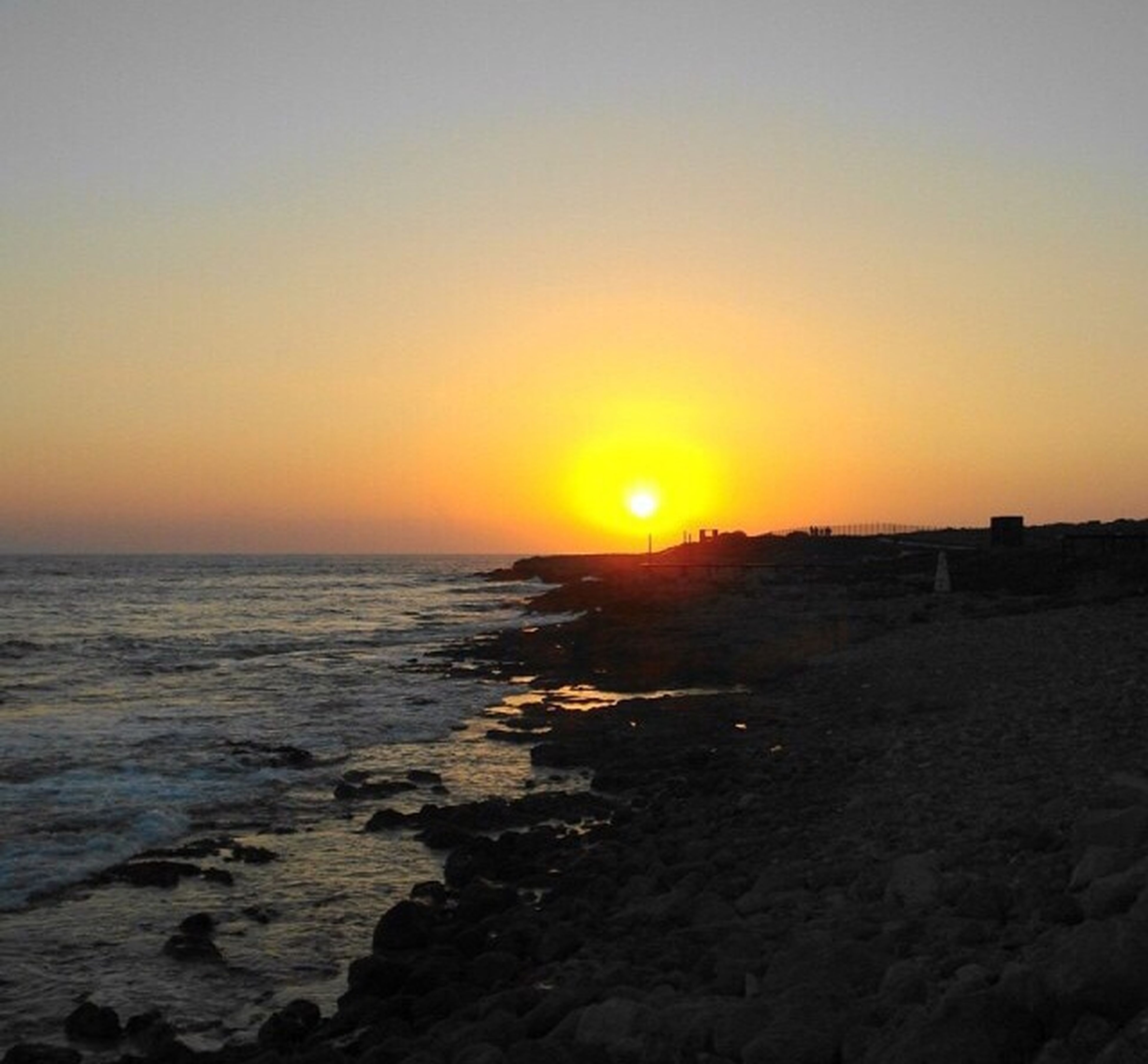 sunset, water, sea, scenics, sun, tranquil scene, orange color, horizon over water, beauty in nature, tranquility, clear sky, beach, copy space, idyllic, nature, shore, rock - object, sky, sunlight, remote