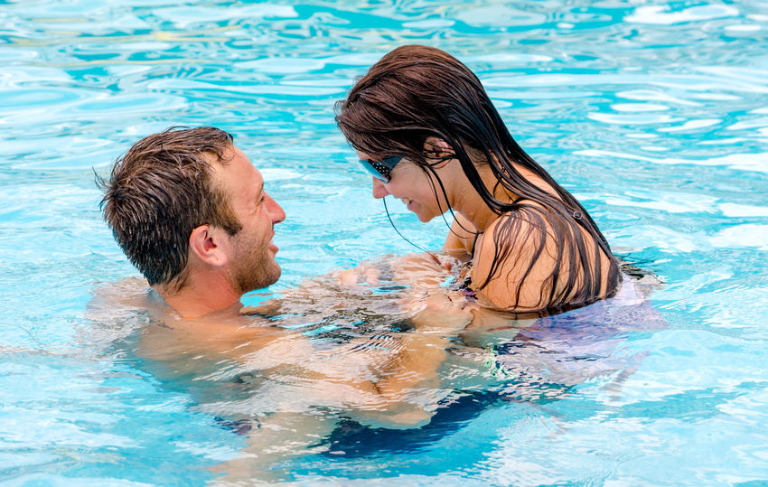 a couple lovingly flirt while swimming in a summertime pool Females Love Man Summertime Woman Bonding Caucasian Day Enjoyment Flirting Happiness Leisure Activity Love Outdoors Outdoors Photograpghy  Relaxation Smiling Summer Swimming Pool Togetherness Vacations Water Water Surface Young Adult