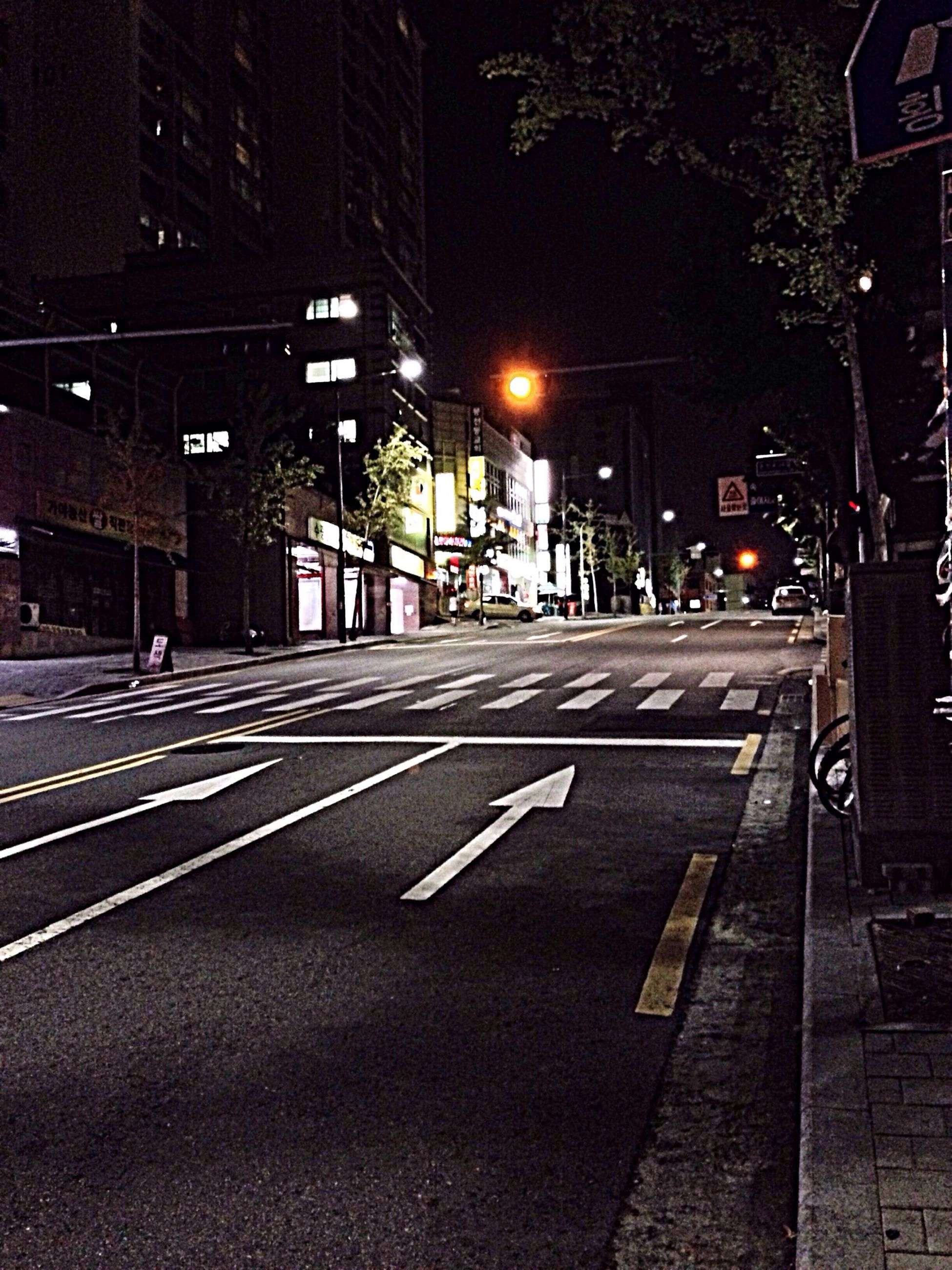 building exterior, illuminated, night, architecture, built structure, transportation, street light, city, street, the way forward, road marking, road, lighting equipment, empty, diminishing perspective, outdoors, city street, city life, building, railroad track