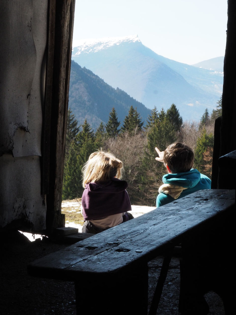 Beauty In Nature Blond Hair Building Exterior Day Full Length Mountain Nature Outdoors People Rear View Relaxation Simple Living Sitting Sky Sunlight Togetherness Two People Wood - Material