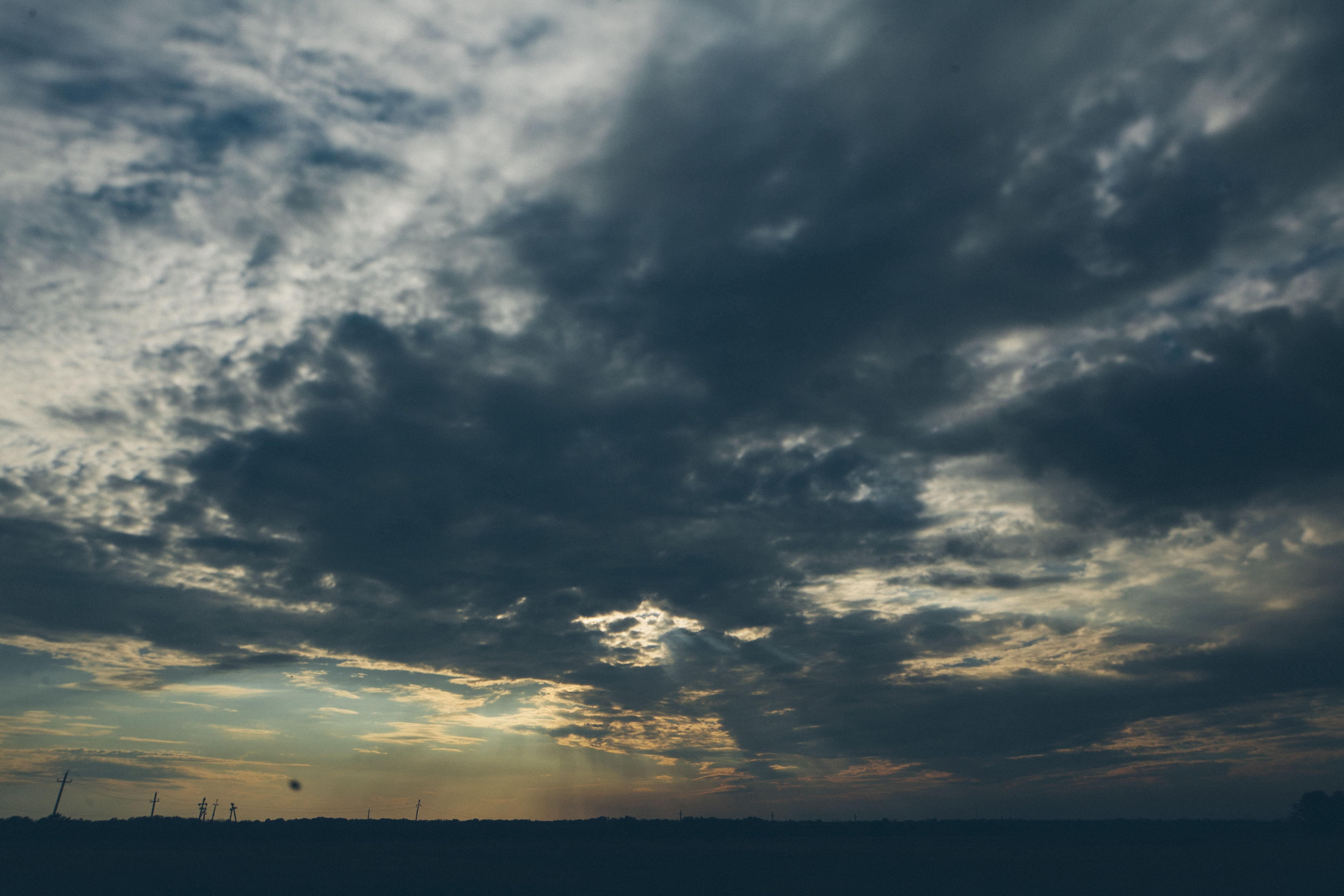 sky, tranquil scene, scenics, cloud - sky, tranquility, beauty in nature, cloudy, sunset, nature, silhouette, cloud, idyllic, weather, cloudscape, overcast, sea, low angle view, outdoors, horizon over water, landscape