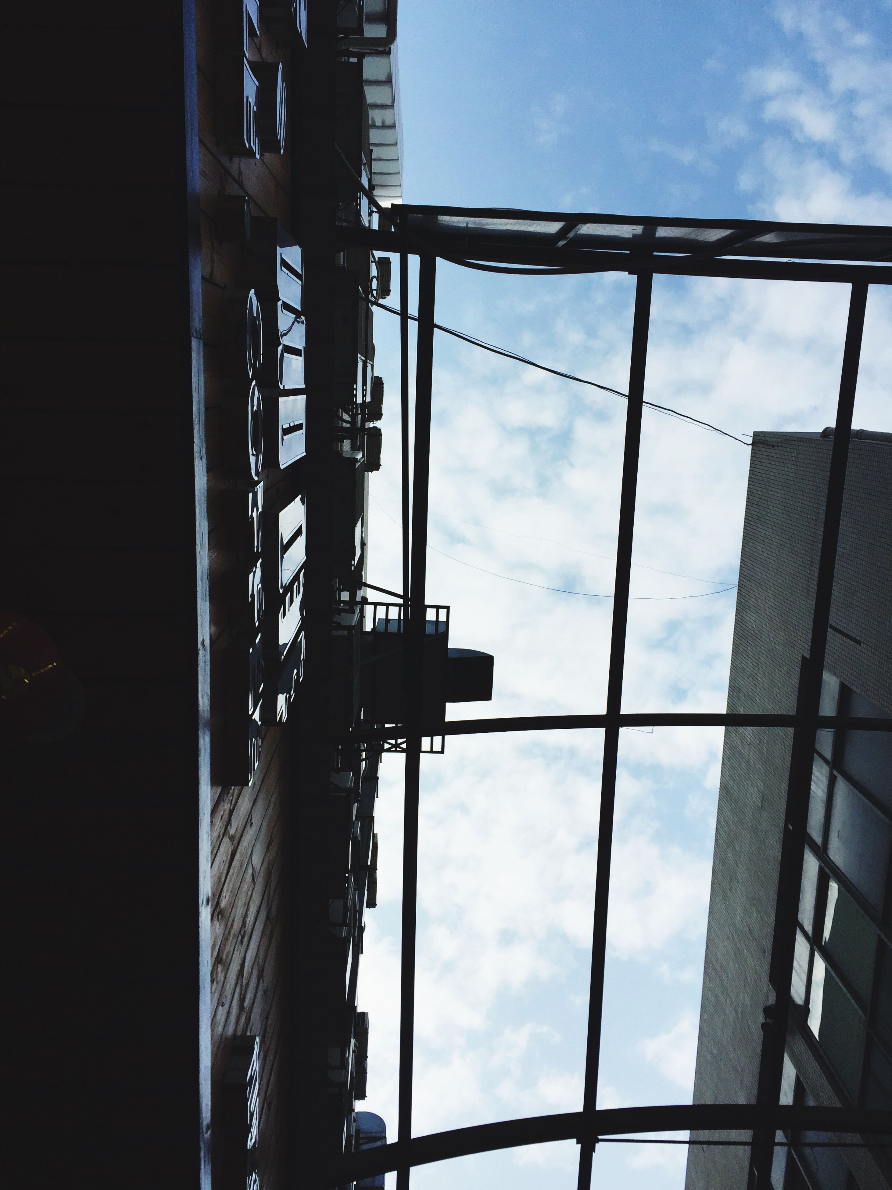 low angle view, built structure, architecture, sky, building exterior, cloud - sky, metal, glass - material, day, building, cloud, window, outdoors, city, cloudy, metallic, no people, modern, reflection, construction site