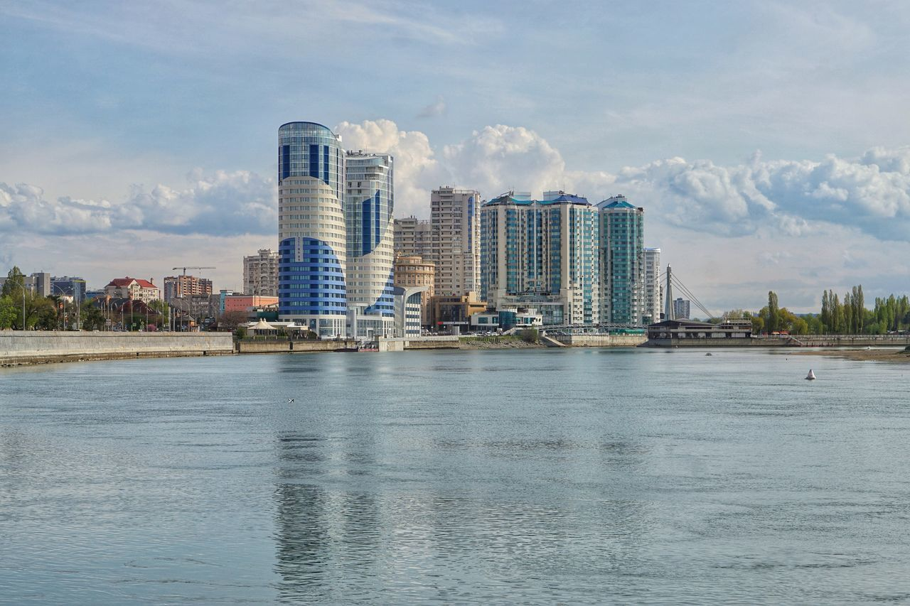waterfront, architecture, building exterior, water, built structure, city, skyscraper, sky, river, cloud - sky, day, outdoors, no people, modern, cityscape, urban skyline, nature