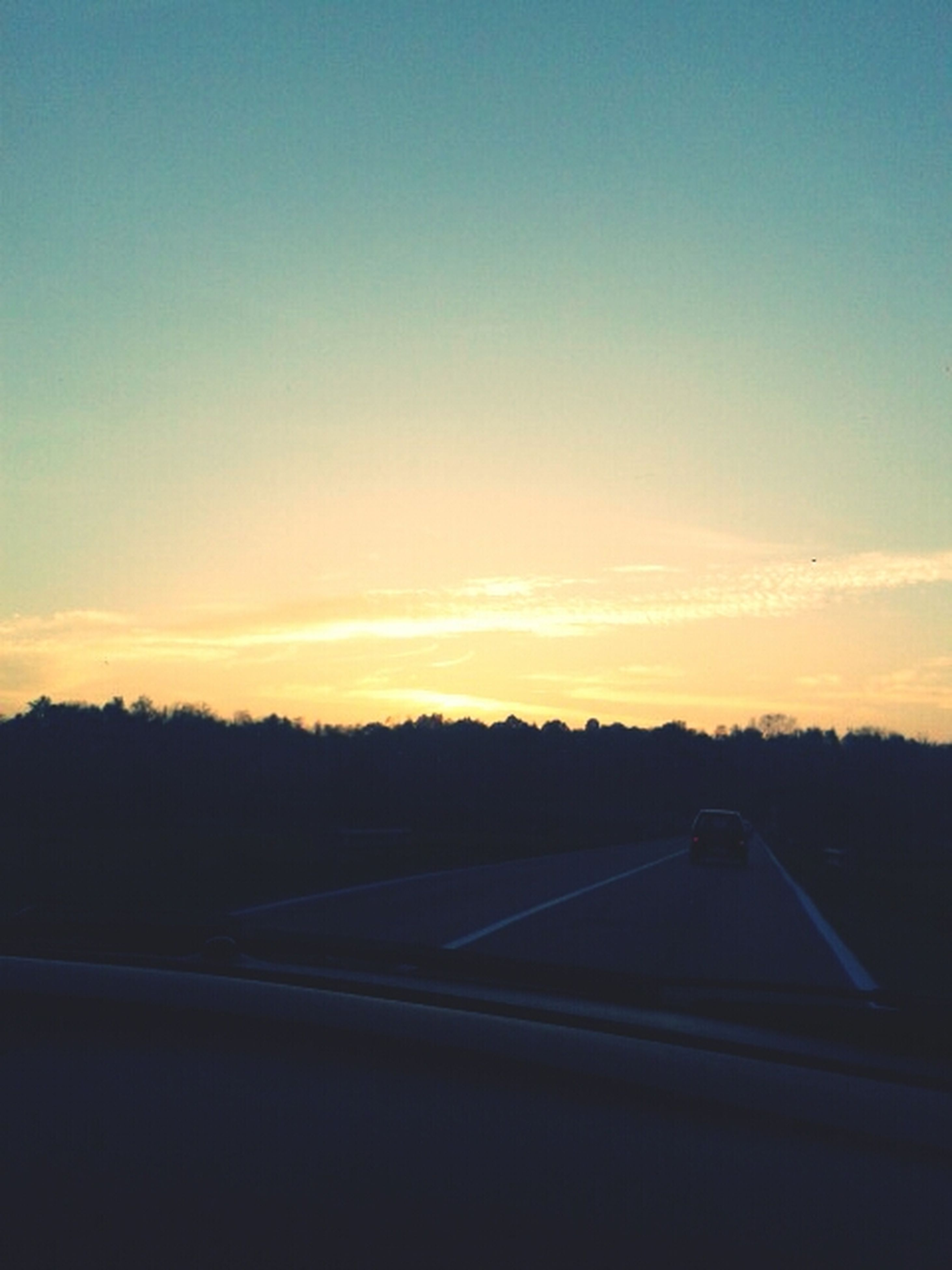 transportation, sunset, silhouette, sky, road, copy space, mode of transport, car, landscape, dusk, scenics, nature, beauty in nature, land vehicle, tranquility, clear sky, no people, tranquil scene, dark, road marking