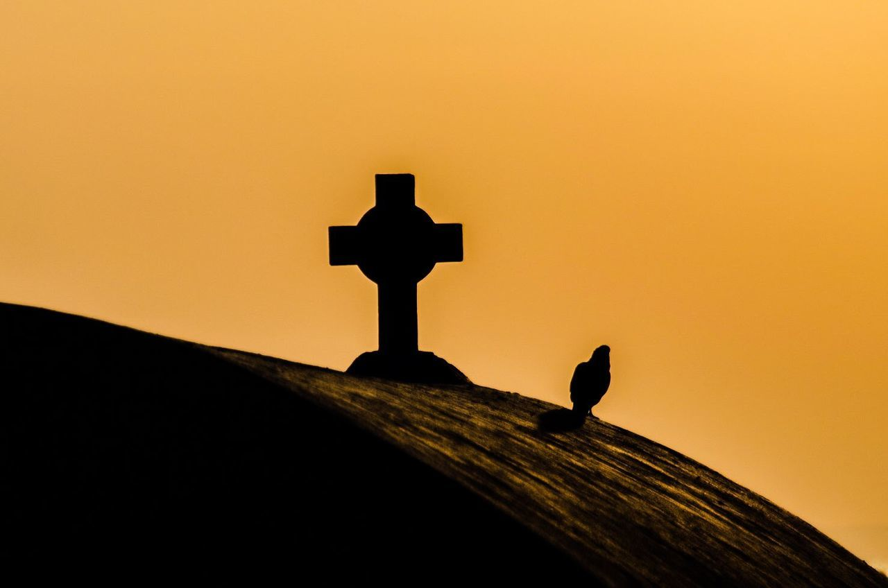 Low Angle View Of Silhouette Cross Against Clear Orange Sky During Sunset