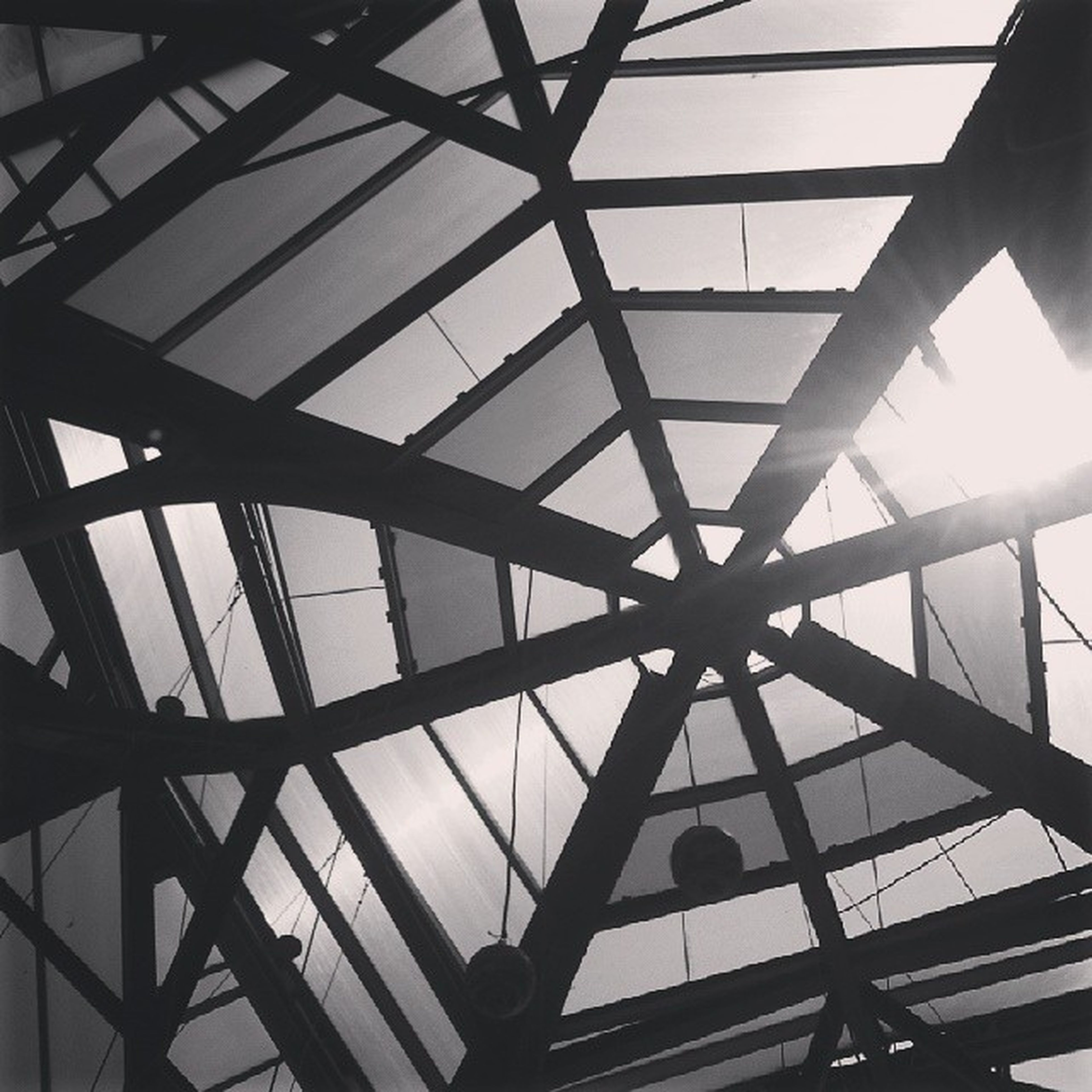 low angle view, built structure, architecture, sky, indoors, metal, ceiling, pattern, transportation, engineering, silhouette, bridge - man made structure, glass - material, metallic, no people, sunlight, day, architectural feature, directly below, geometric shape