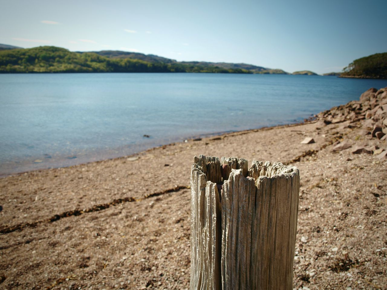 Shieldaig Scotland Highlands Loch  Beach Water Lake Mountain Wooden Post Landscape Tranquility Outdoors Scenics No People Beauty In Nature Hills Pebbles Day Sky Blue Sky Clear Sky The Great Outdoors - 2017 EyeEm Awards Close-up