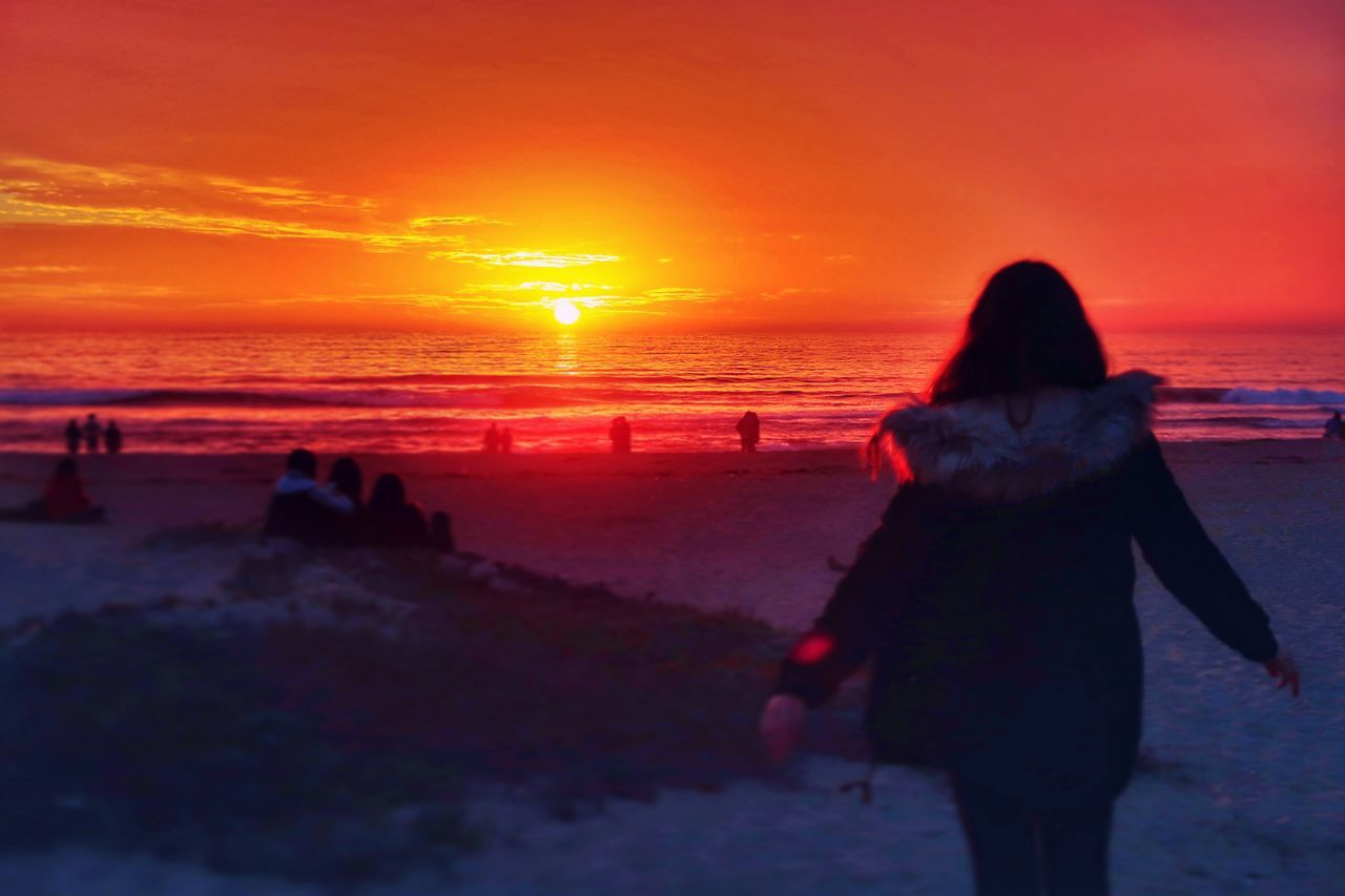 sunset, sea, beach, rear view, beauty in nature, orange color, nature, horizon over water, real people, silhouette, scenics, leisure activity, sky, lifestyles, walking, women, sun, water, one person, tranquil scene, vacations, tranquility, outdoors, sand, full length, standing, wave, adult, people