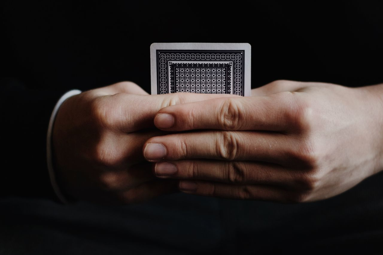 Hands holding hidden playing card Adult Bet Betting Black Background Card Casino Close-up Concept Elegant Gamble Game Holding Human Body Part Human Hand One Person Play Poker RISK Secrecy Secret Single Studio Shot Success Unknown Win
