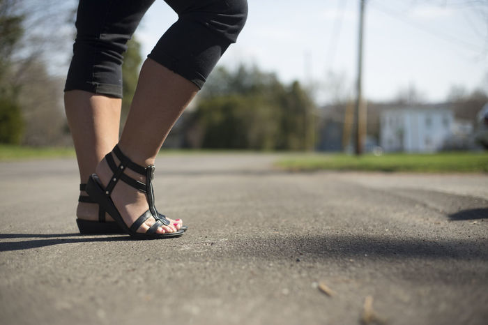 A woman's lower half posing with foot pointed up. Black Copy Space Day Time Feet Horizontal Legs Lower Half Lower Half Tooday Pants Pose Poser Road Standing Street Summer