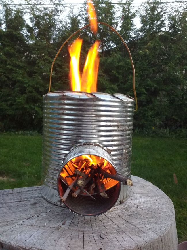 A simple Rocket Stove made from four cans, a hanger, and earth. Rocket Stove Burning Flame Lawn Fire - Natural Phenomenon Firewood No People Glowing Orange Color Canada Coast To Coast Eyeem Collection EyeEm Best Shots Popular Campfire Firepit Eye4photography  EyeEm Gallery Fire Vibrant Color Simplicity Cooking Fire Pit Aluminum Can Survival Branches