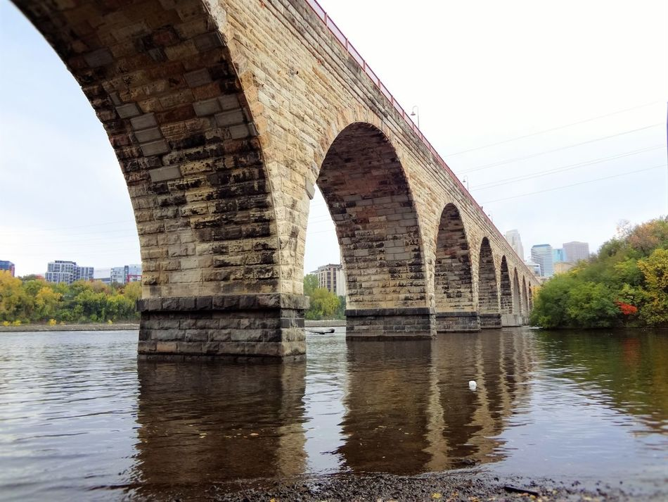 St. Anthony Main trails in Minneapolis MN Arch Architecture Bridge Bridge - Man Made Structure Built Structure Clear Sky Connection Day History Nature No People Outdoors Reflection River Sky Stone Tabphotography Travel Destinations Tree Water Water Reflections Waterfront