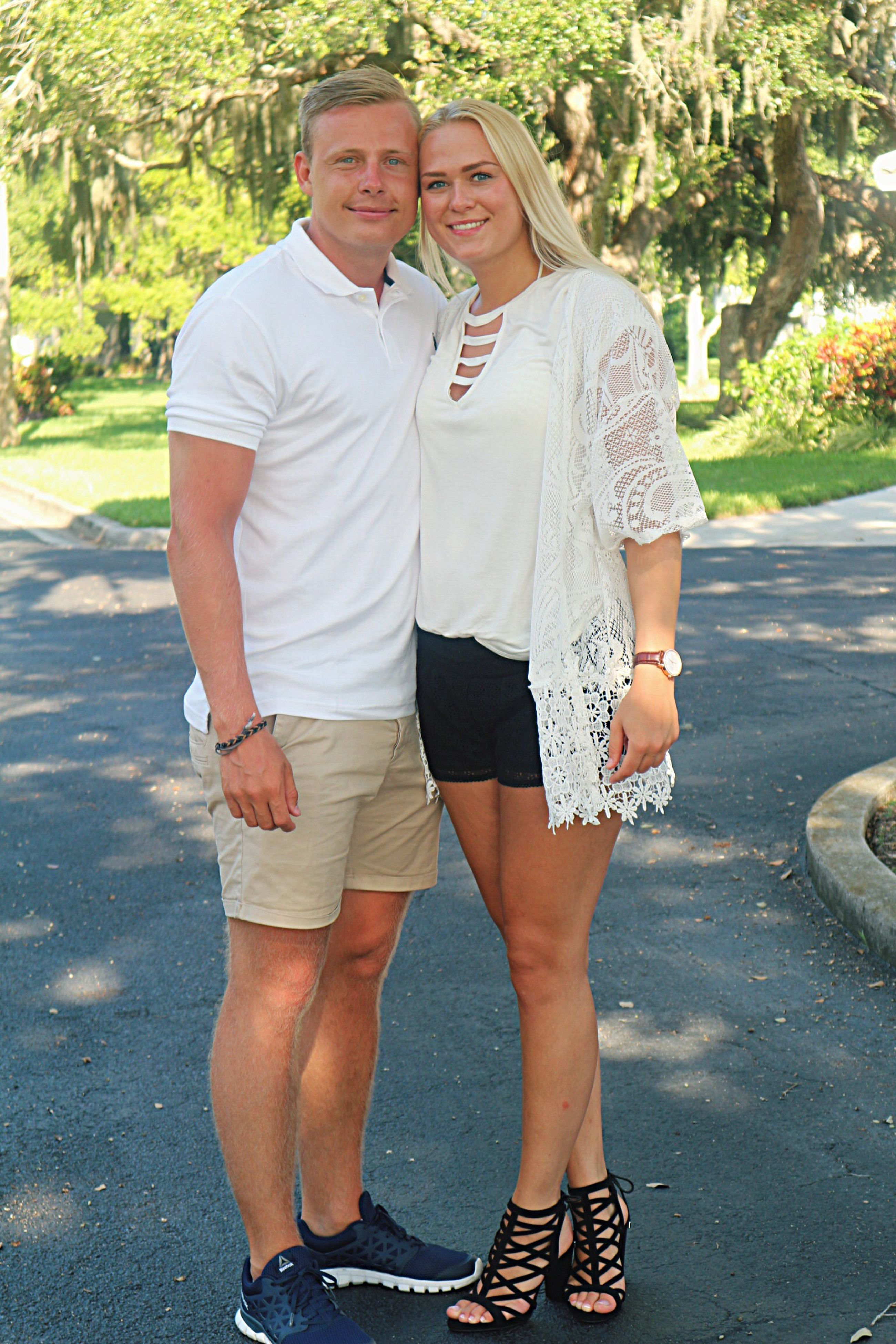 two people, love, togetherness, heterosexual couple, casual clothing, full length, portrait, front view, looking at camera, shorts, couple - relationship, bonding, real people, happiness, outdoors, standing, day, young women, young adult, leisure activity, road, lifestyles, embracing, smiling, men, beautiful woman, adults only, adult, people