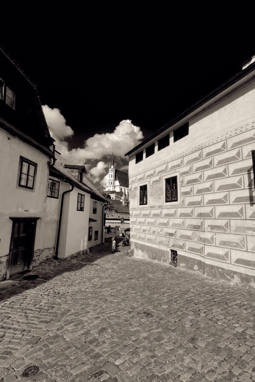 Street Amidst Houses Leading Towards Church Against Sky