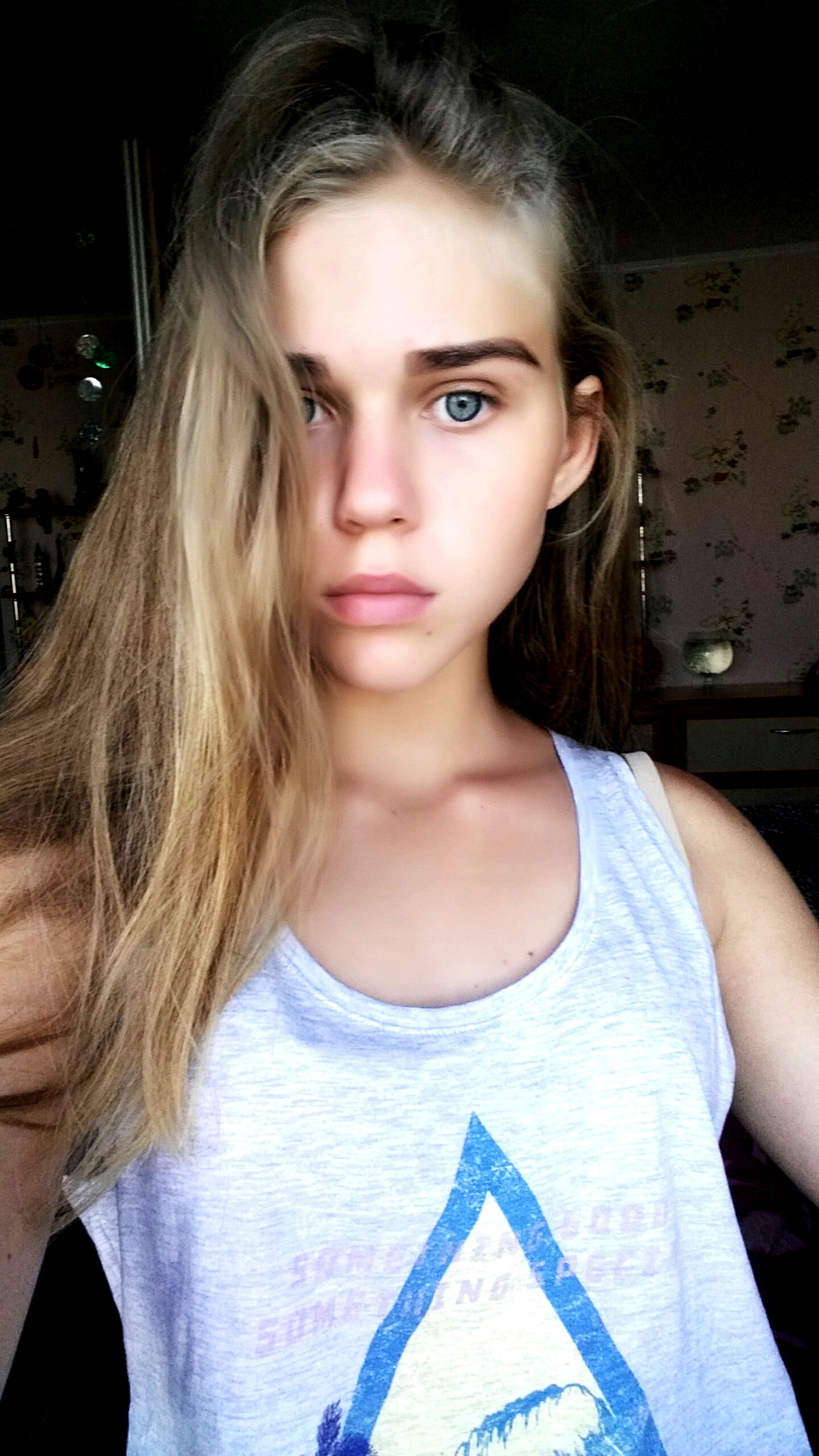 looking at camera, real people, one person, blond hair, front view, portrait, young adult, casual clothing, young women, beautiful woman, long hair, indoors, medium-length hair, standing, lifestyles, day, close-up, people
