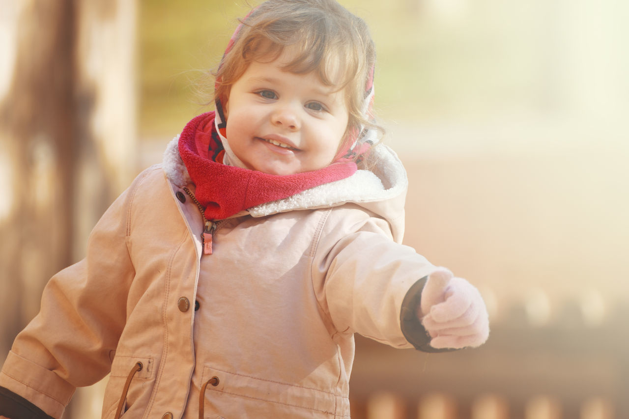 A happy smiling girl playing in the park. Autumn sunset, Autumn Child Childhood Day Girl Gloves Happiness Jacket Looking At Camera Nature Outdoors Park, Playing Smiling Thumbs Up Warm Clothing