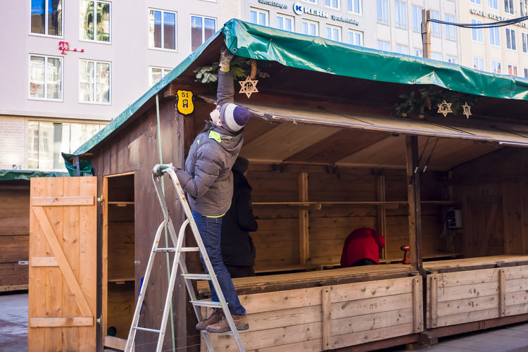 Dismantling market stall at Munich Christmas market in Marienplatz, Germany. Christmas Christmas Market Dismantling Architecture Building Exterior Built Structure Editorial  End Full Length Men Occupation One Person Outdoors People Real People Seasonal Stall Working