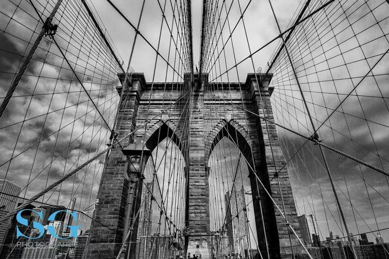 architecture, built structure, bridge - man made structure, connection, low angle view, arch, day, sky, suspension bridge, transportation, building exterior, travel destinations, outdoors, no people, city