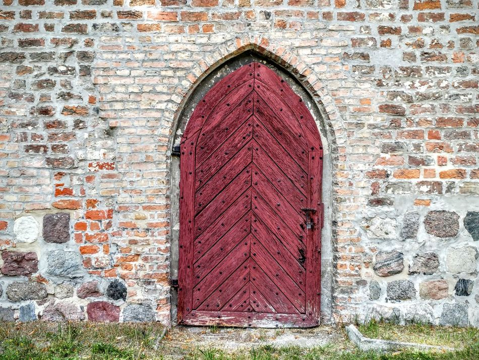 Old Red- Violet Wooden Door in Stone Wall