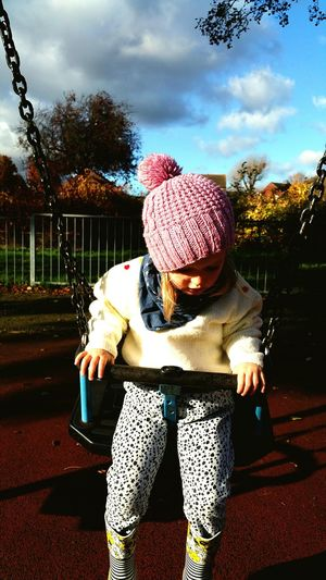 Childhood One Person Outdoors Child Warm Clothing Hand Knitted 2 Years Old Mothers Love Swing Playground Crane Park Twickenham Autumn Winter Park - Man Made Space Sky Daughter England Children swing Bobble Hat  Pinkswinging People Senior Adult Day Adult Full Length