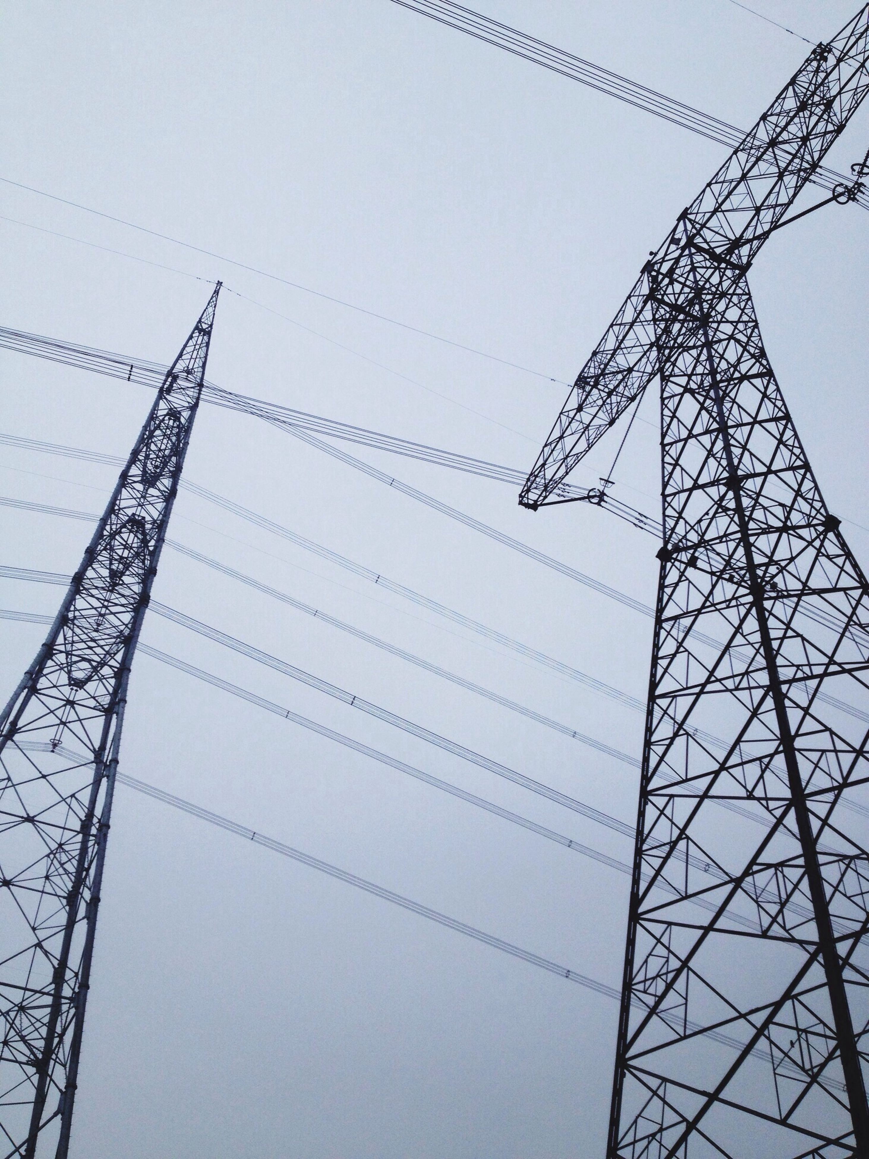 low angle view, power line, clear sky, fuel and power generation, electricity pylon, power supply, electricity, built structure, connection, technology, cable, architecture, sky, building exterior, tall - high, day, outdoors, no people, tower, copy space