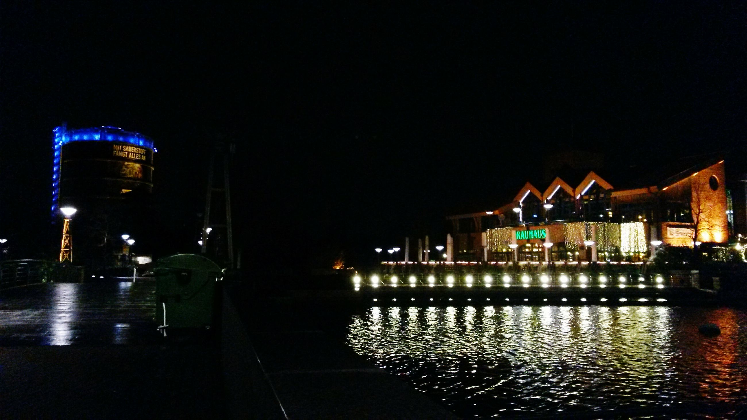 night, illuminated, building exterior, architecture, built structure, water, city, reflection, clear sky, street, street light, copy space, lighting equipment, waterfront, building, transportation, outdoors, city life, wet, sky