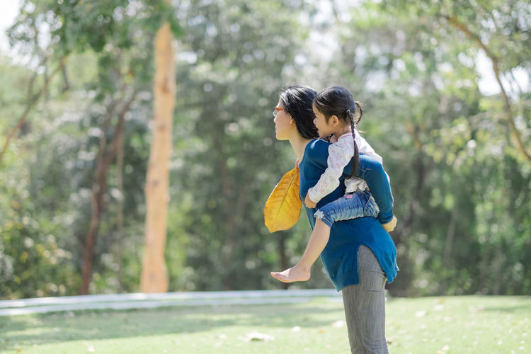 Adult Casual Clothing Child Day Eco Tourism Forest Friendship Girl Leisure Activity Mother Mother And Daughter Nature Outdoors People Piggyback Single Mother Sports Clothing Togetherness Tree Two People Women Young Adult