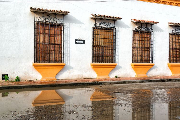 Windows on a colonial wall reflected in water on the ground in Mompox, Colombia Architecture Building Building Exterior Built Structure Colombia Colonial Colonial Architecture Historic Historical Building Landmark Magdalena River Mompos Mompox  Old Residential Building Residential Structure Rio Magdalena Santa Cruz De Mompox South America Town Unesco UNESCO World Heritage Site Urban White Window