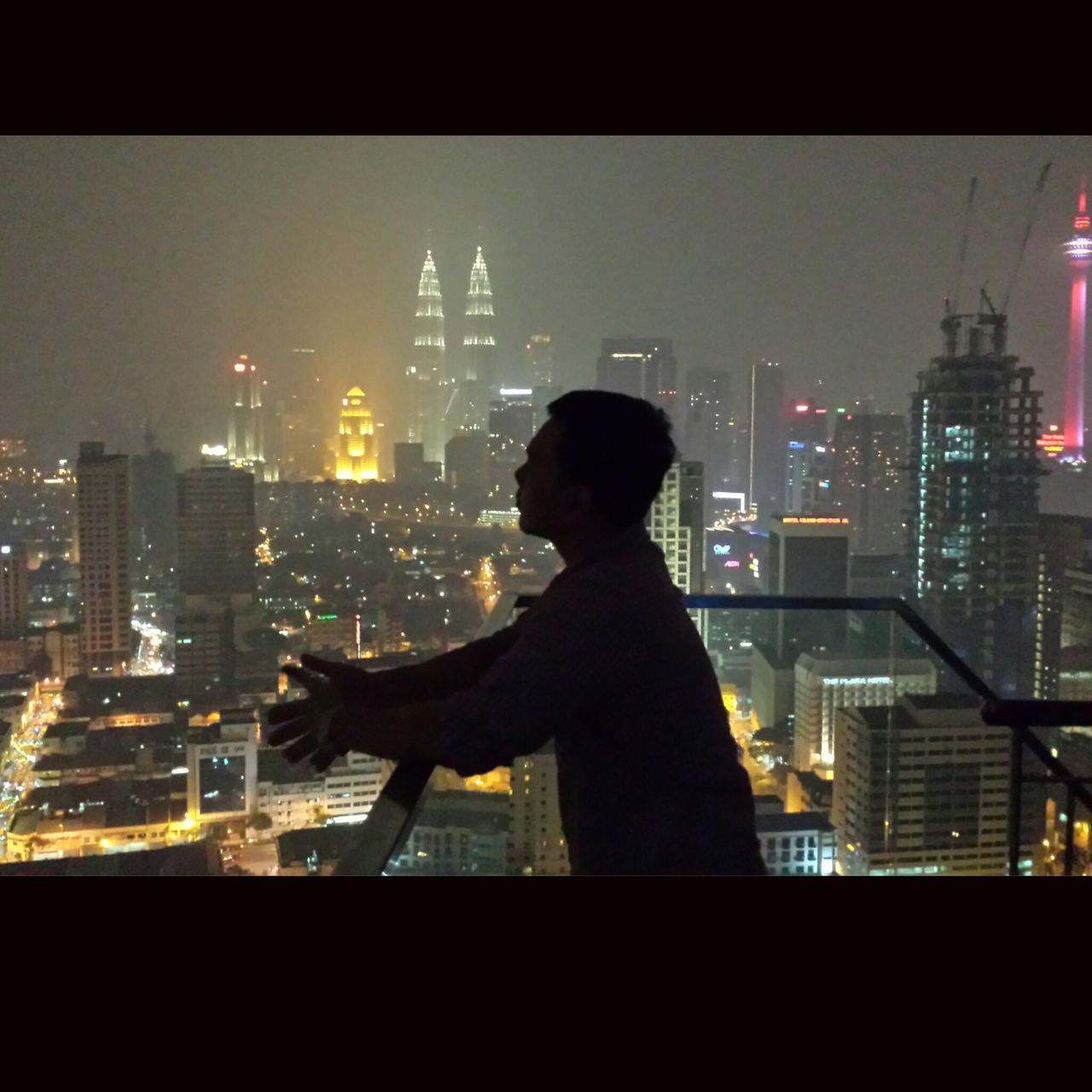 city, cityscape, architecture, skyscraper, building exterior, built structure, real people, illuminated, city life, night, one person, men, urban skyline, silhouette, modern, lifestyles, side view, travel destinations, standing, sky, outdoors